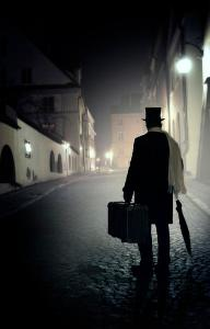 victorian-man-with-top-hat-carrying-a-suitcase-walking-in-the-old-town-at-night-jaroslaw-blaminsky